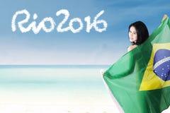 Modello femminile con la bandiera brasiliana alla costa Fotografie Stock Libere da Diritti