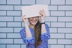 Modello femminile con un libro bianco sulla parete del fondo Immagine Stock Libera da Diritti