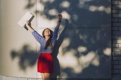 Modello femminile con un libro bianco sulla parete del fondo Fotografie Stock Libere da Diritti