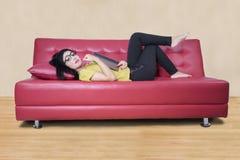 Modello femminile con un romanzo sul sofà Immagini Stock
