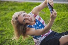 Modello femminile contro un prato inglese in una maglietta con una bandiera americana a Fotografie Stock