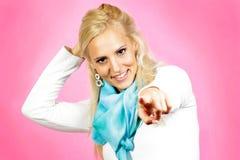Modello femminile dei capelli leggeri, vestito con indifferenza, indicante con il suo dito Fotografia Stock
