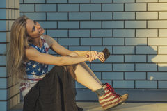 Modello femminile sui precedenti di una costruzione in una maglietta con la a Immagini Stock