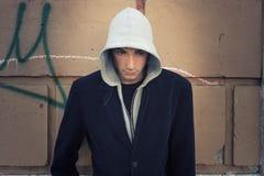 Modello fresco dell'uomo con la maglia con cappuccio, fondo della parete fotografia stock libera da diritti