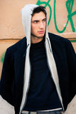Modello fresco dell'uomo con la maglia con cappuccio, fondo urbano della parete Immagini Stock