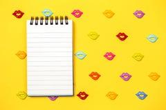 Modello giallo allegro delle labbra con il blocco note fotografia stock