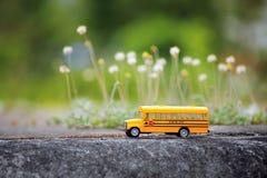 Modello giallo del giocattolo dello scuolabus sulla strada campestre Fotografie Stock