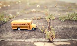 Modello giallo del giocattolo dello scuolabus sulla strada campestre Immagini Stock