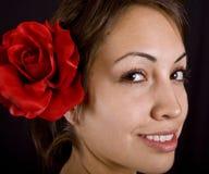 Modello grazioso con il fiore rosso in suoi capelli immagini stock