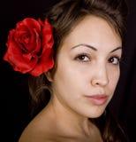 Modello grazioso con il fiore in suoi capelli immagine stock