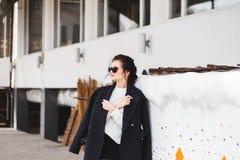 Modello grazioso della donna di modo che porta un cappotto scuro e un maglione bianco, in occhiali da sole, posanti sopra il fond immagine stock libera da diritti