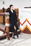 Modello grazioso della donna di modo che porta un cappotto scuro e un maglione bianco che posano sopra l'origine etnica immagini stock libere da diritti