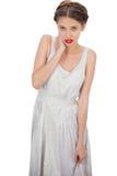 Modello imbarazzante in vestito bianco che posa mano sul collo Fotografia Stock