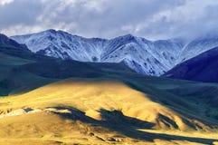 Modello leggero di tramonto sulla cima della collina e pendii con il cielo nuvoloso Immagine Stock Libera da Diritti