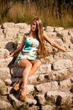 Modello lungo caucasico dei capelli sulle rocce Immagini Stock