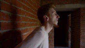 Modello maschio contro un fondo del muro di mattoni grigio video d archivio