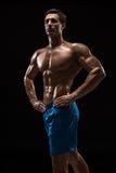 Modello maschio giovane di forma fisica muscolare ed adatta del culturista che posa sopra il fondo nero Fotografia Stock