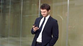 Modello maschio in vestito di affari Condizione felice dell'uomo d'affari, sorridere, esaminante macchina fotografica video d archivio