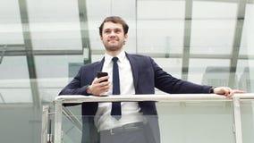 Modello maschio in vestito di affari Condizione felice dell'uomo d'affari, sorridere, esaminante macchina fotografica archivi video