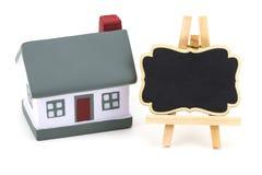 Modello miniatura del bene immobile della casa per l'etichetta di affitto sul BAC bianco Fotografia Stock