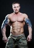 Modello muscoloso con il tatuaggio Immagine Stock