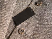 Modello nero in bianco del prezzo da pagare dell'etichetta sul cappotto marrone immagine stock libera da diritti
