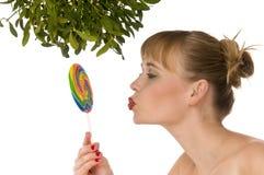 Modello nudo che bacia un lollipop sotto il vischio Immagini Stock Libere da Diritti