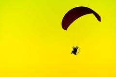 Modello nuvoloso del fondo della luce di giallo tramonto della siluetta di Paramotor immagine stock libera da diritti