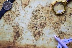 Modello, orologio e lente dell'aeroplano sopra la mappa d'annata immagine stock