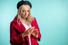 Modello piacevole in cappotto e berretto che esaminano lo smartphone immagine stock