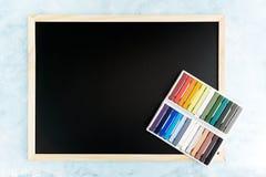 Modello posteriore della lavagna con i gessi variopinti su fondo blu-chiaro Affare, interior design, segnante concetto con letter Fotografia Stock