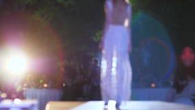 Modello professionale nel vestito da sera bianco che cammina lungo la passerella all'illuminazione dei riflettori in unfocused video d archivio