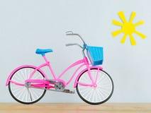 Modello rosa della bicicletta del ` s dei bambini sul pavimento di legno contro lo sfondo del sole di giallo del giocattolo Immagini Stock