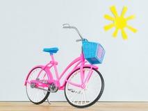 Modello rosa della bicicletta del ` s dei bambini sul pavimento di legno contro lo sfondo del sole del giocattolo Immagini Stock Libere da Diritti