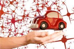 Modello rosso dell'automobile del giocattolo sopra la mano della donna Fotografia Stock Libera da Diritti