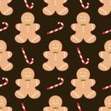 Modello senza cuciture con i biscotti e la caramella casalinghi dell'uomo di pan di zenzero di Natale tradizionale su fondo scuro Fotografia Stock