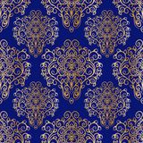 Modello senza cuciture con l'ornamento dorato disegnato a mano su un fondo blu Fotografia Stock