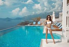 Modello sexy in bikini bianco che prende il sole dalla piscina di infinito fotografia stock libera da diritti