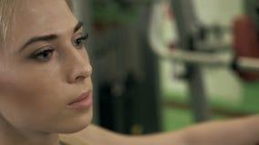 Modello sexy del ritratto e un corpo abbronzato esile del ` s della donna che distoglie lo sguardo nella palestra di forma fisica archivi video