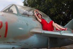 Modello sorridente di pin-up sull'ala dell'aeroplano Fotografia Stock Libera da Diritti