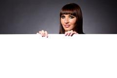 Modello in studio dietro il grande segno in bianco Fotografia Stock Libera da Diritti