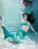 Modello subacqueo in uno stagno che indossa una coda delle sirene Immagine Stock