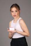 Modello teenager che mostra carta bianca Fine in su Fondo grigio Fotografie Stock