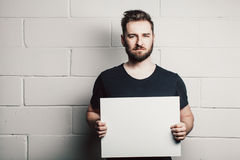Modello vuoto bianco dello spazio in bianco della carta della tenuta dell'uomo della barba Fotografie Stock Libere da Diritti