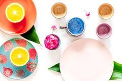 Modello vuoto del piatto Tazze e piatti vicino alle foglie tropicali e frutti sulla vista superiore del fondo bianco Immagini Stock