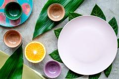 Modello vuoto del piatto Tazze e piatti vicino alle foglie tropicali e frutti sulla vista superiore del fondo grigio Fotografia Stock Libera da Diritti