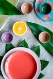 Modello vuoto del piatto Tazze e piatti vicino alle foglie tropicali e frutti sulla vista superiore del fondo grigio Fotografia Stock