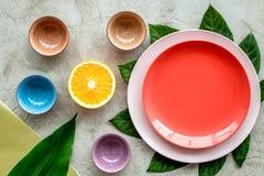 Modello vuoto del piatto Tazze e piatti vicino alle foglie tropicali e frutti sulla vista superiore del fondo grigio Immagine Stock