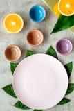 Modello vuoto del piatto Tazze e piatti vicino alle foglie tropicali e frutti sulla vista superiore del fondo grigio Immagine Stock Libera da Diritti