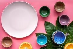 Modello vuoto del piatto Tazze e piatti vicino alle foglie tropicali e frutti sulla vista superiore del fondo rosa Fotografia Stock